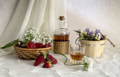 Still life with strawberries. Brandy and wild iris on a table close-up Stock Photography