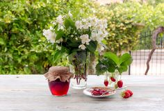 Still life with strawberry jam and bouquet of jasmine stock photography