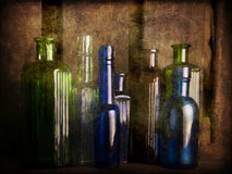 Still Life Study with old glass coloured bottles. With textured wooden crate as backdrop Royalty Free Stock Photography