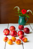 Still life with summer flowers and fruits on wooden table. Stock Photos