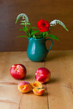 Still life with summer flowers and fruits on wooden table. Stock Photography