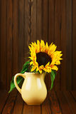 Still life with sunflower in vase on wooden background. Stock Image