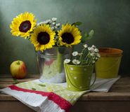 Still life with sunflowers, buckets and apple. On wooden table Royalty Free Stock Photography