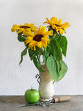 Still life of sunflowers. Still life picture of sunflowers with an apple, knife and sunflower seeds placed on an old wooden table Royalty Free Stock Photos