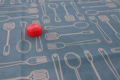 Red bottle cap on blue table cloth with images of spoon and fork stock photography