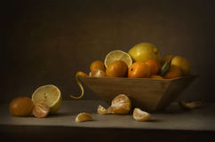 Still life tangerines and lemons. In a wooden bowl stock photography