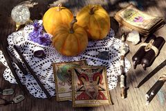 Still life with tarot cards, pumpkins, black candles and runes on old planks royalty free stock photos