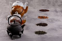 Still life for a tea card. Different varieties of tea leaves and a variety of forms of teapots. The concept of tea drinking royalty free stock image