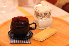 Still life tea drinking. Cup with drink, a wafer with a napkin on a cloth Royalty Free Stock Image