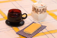 Still life tea drinking. Cup with drink, a wafer with a napkin on a cloth Stock Photography