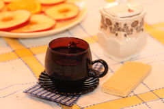 Still life tea drinking. Cup with drink, a wafer with a napkin on a cloth royalty free stock photos
