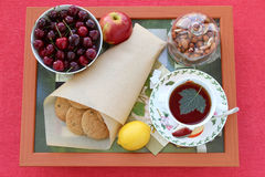 Still life with tea, homemade oatmeal cookies with raisins, cherries, lemon, apple, nuts and lump sugar on a wooden tray Stock Photo