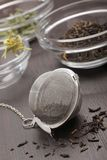 Still life with tea infuser. Tea infuser with black tea dried leaves lying on dark board with unfocused background Royalty Free Stock Photos