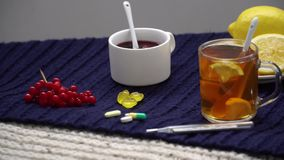Still life of tea with lemon, tablets and thermometer, jam and berries. The concept of treating colds.  stock footage