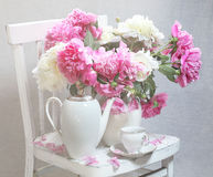 Still-life with tea and peonies. Still-life with white service and a bouquet from pink and white peonies royalty free stock images