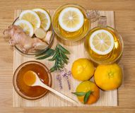 Still life. Tea in transparent cups. Honey, ginger, lemon and tangerines. From cold and flu. royalty free stock photography