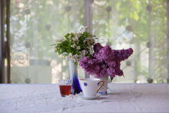 Still-life with tea, wine and a lilac bouquet Royalty Free Stock Photography