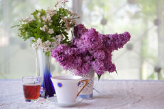 Still-life with tea, wine and a lilac bouquet Stock Image