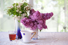 Still-life with tea, wine and a lilac bouquet Stock Photos
