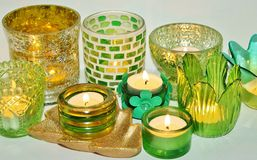 Still life of Tealight holders. Still life of an Arrangement of green and golden glass tealight holders with burning tea candles Stock Photo