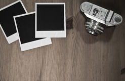 Still life three blank instant photo frames on old wooden background with old retro vintage camera with copy space Royalty Free Stock Images