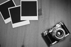 Still life three blank instant photo frames on old wooden background with old retro vintage camera with copy space Stock Photos