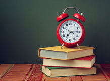 Still life with three books and a red alarm clock. Stock Images