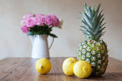 Still life of three lemons and a pineapple Royalty Free Stock Photos