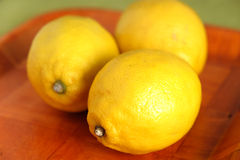 Still life with three ripe yellow lemons on brown tray Royalty Free Stock Photography
