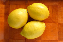 Still life with three ripe yellow lemons on brown tray Stock Images