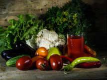 Still life with tomato juice and vegetables. Still life with tomato juice, tomatoes, cucumbers, cauliflower, eggplant and pepper Royalty Free Stock Photography