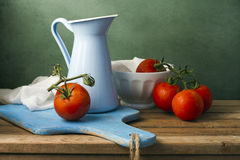Still life with tomatoes and enamel jug Stock Photo