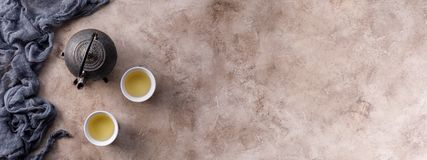 Still life with traditional Asian herbal tea, cooked in an old cast-iron kettle on a textured background with a bowl. Banner stock photo