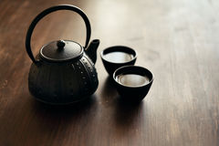 Still life with traditional eastern teapot and teacups on wooden desk Stock Photos