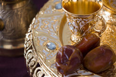 Still life with traditional golden arabic coffee set with dallah, coffee pot jezva, cup and dates. Dark background. Horizontal photo Stock Photography