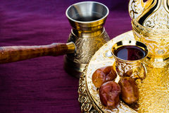 Still life with traditional golden arabic coffee set with dallah. Coffee pot & x28;jezva& x29;, cup and dates. Dark background. Horizontal photo Stock Photography
