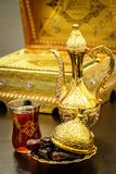 Still life with traditional luxury golden arabic coffee set with dallah, cup and dates. Quran book background. Ramadan concept stock photography