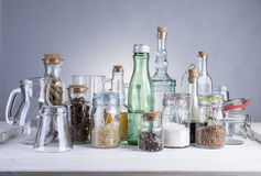 Still life of transparent glass bottles, cans and glasses. Still life of transparent glass bottles, cans and glasses on a white wooden table Stock Photo