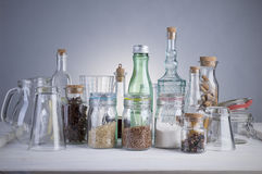 Still life of transparent glass bottles, cans and glasses. Stock Photo