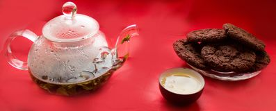 Still life, transparent glass teapot, cup with tea, cookies Royalty Free Stock Photo