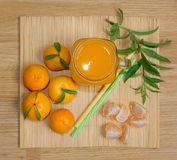 Still life. A transparent mug with a handle with freshly squeezed tangerine juice. And fresh tangerines. royalty free stock photography