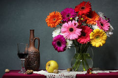 Still life with Transvaal daisies, apples and red wine. Royalty Free Stock Photos