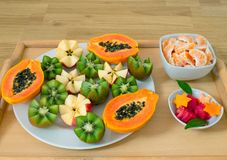 Still life. A tray with papaya, kiwi, apples. Pieces of tangerines and watermelon in plates. stock photo