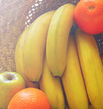 Still life with tropical fruits: bananas,  oranges ,  on a concrete surface in the sunlight. Royalty Free Stock Photography