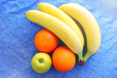 Still life with tropical fruits: bananas,  oranges ,  on a concrete surface in the sunlight. Royalty Free Stock Images