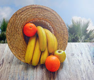 Still life with tropical fruits: bananas,  oranges ,  on a concrete surface in the sunlight. Stock Image