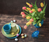 Still life with tulips and dishes. Still life with tulips and blue and green dishes, sweets easter eggs on a dark background stock photo