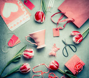 Still life with tulips, pink cup, shopping bag, gift box, shear and paper envelope with heart, top view, Flat lay styling. Mothers Royalty Free Stock Photo