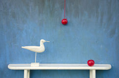 Still-life with two apple and white bird sculpture on shelf. Still-life with two red apple and white bird sculpture on shelf Royalty Free Stock Image