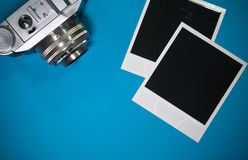 Still life two blank instant photo frames on blue background with old retro vintage camera with copy space Stock Photos